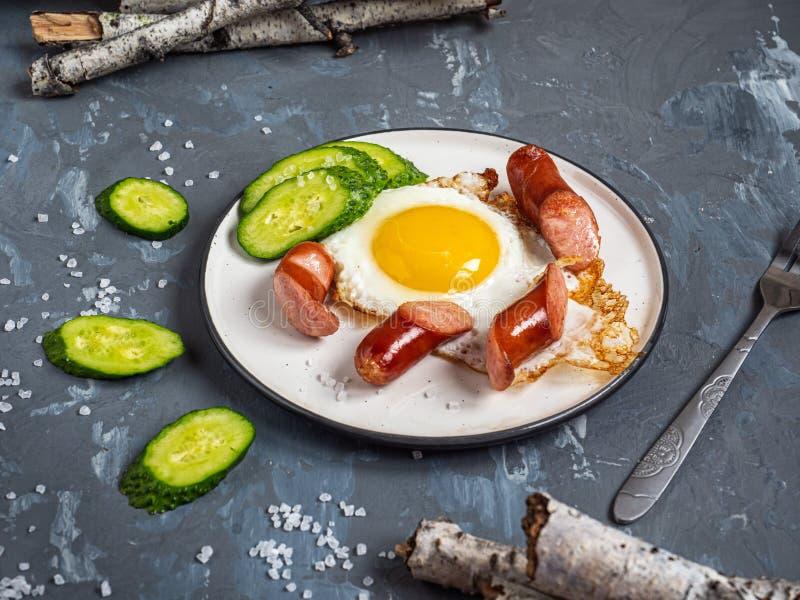 Fr?hst?ck von durcheinandergemischten Eiern mit der Jagd von W?rsten und von Scheiben der Gurke lizenzfreies stockfoto