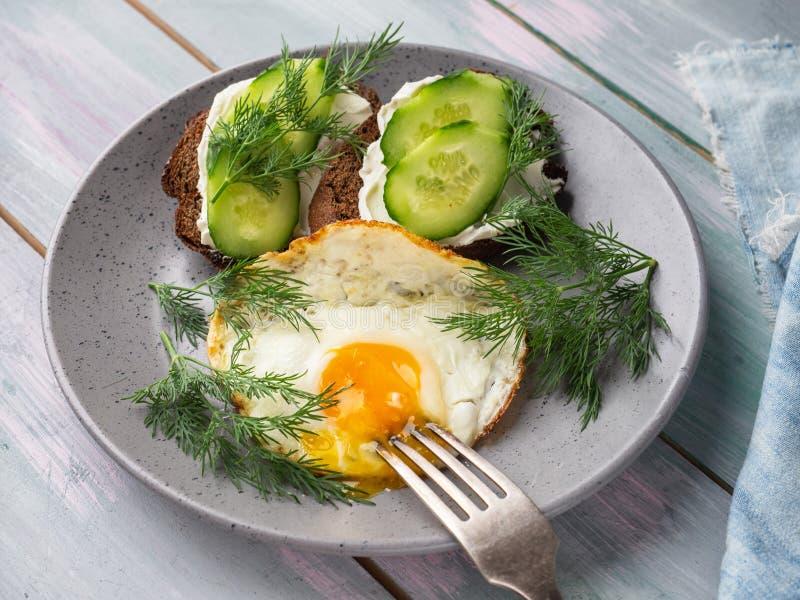 Fr?hst?ck von Eiern und von Toast mit Gurke und Quark diente auf einer grauen keramischen Platte stockfoto