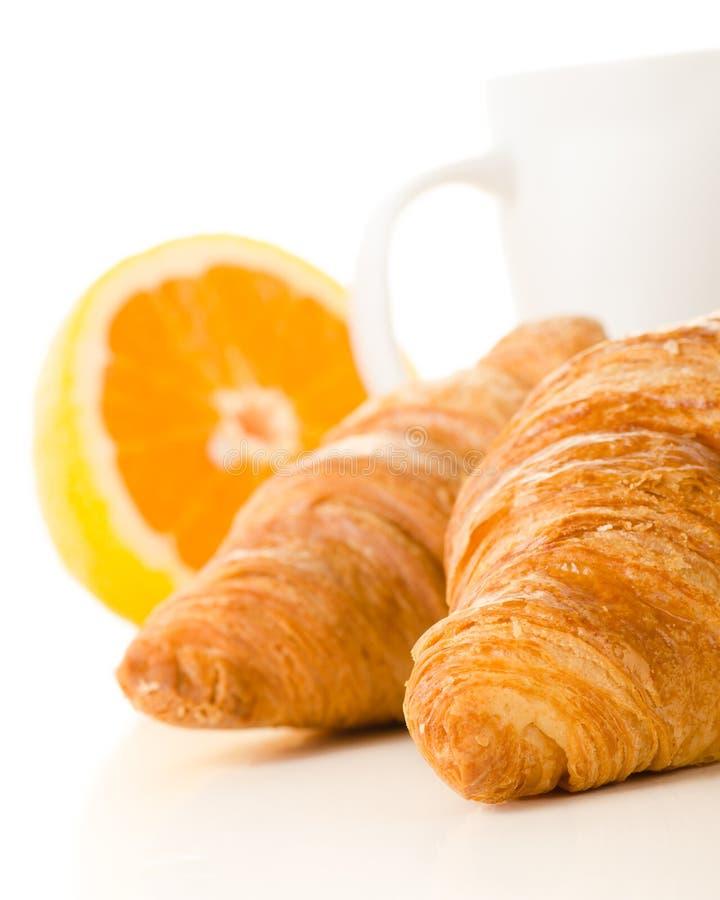 Frühstück von frischen Hörnchen, von Kaffee und von Orange über Weißrückseite lizenzfreie stockbilder