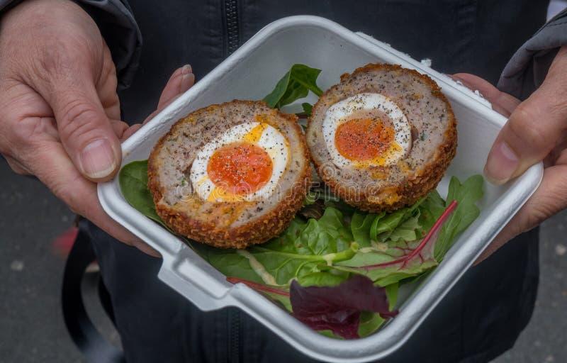 Frühstück von schottischen Eiern und von traditionellem Schweinefleisch u. von Salbei des Gemüsesalats stockfoto