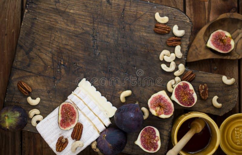 Frühstücken ein Hörnchen mit Feigen und Honig Brie und Nüsse Hölzernes Brett Geometrische Verzierung auf einem alten Papier Brown lizenzfreie stockfotografie