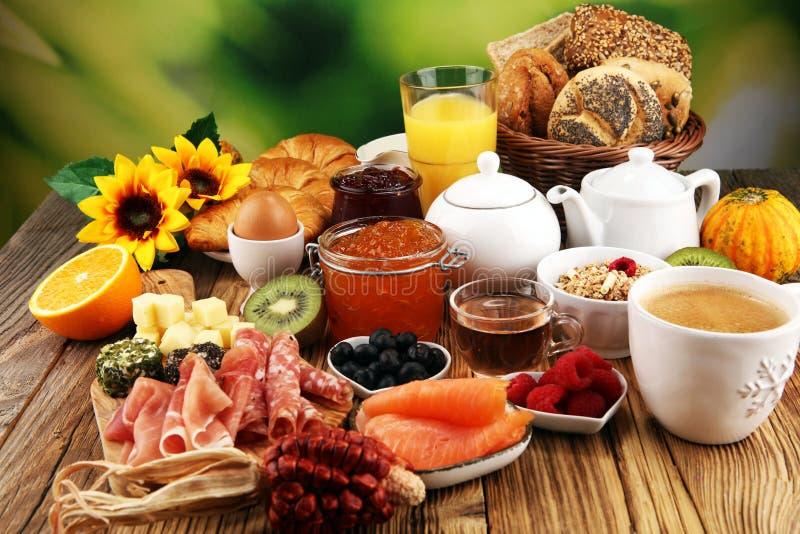 Frühstücken Sie auf Tabelle mit Brotbrötchen, -hörnchen, -coffe und -saft stockfotografie