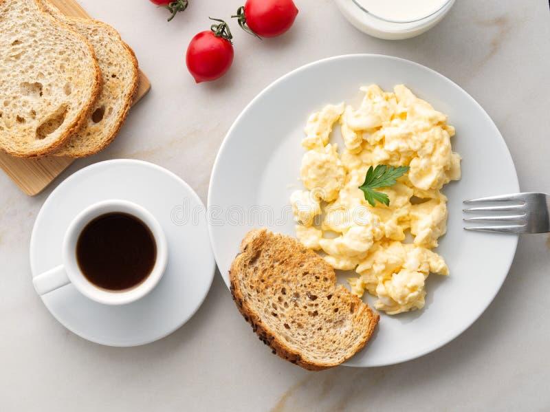 Frühstücken Sie mit Pan-gebratenen durcheinandergemischten Eiern, Tasse Kaffee, Tomaten auf weißem Steinhintergrund Omelett, Drau stockfotos