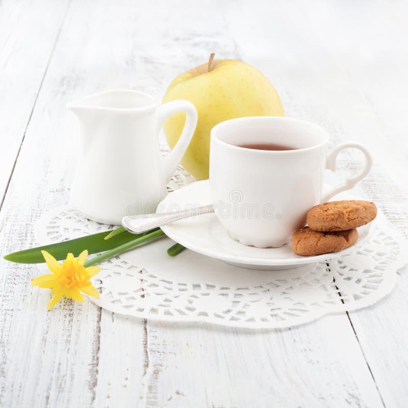 Frühstücken Sie mit selbst gemachten Plätzchen und Apfel, mit Tasse Tee stockfotografie