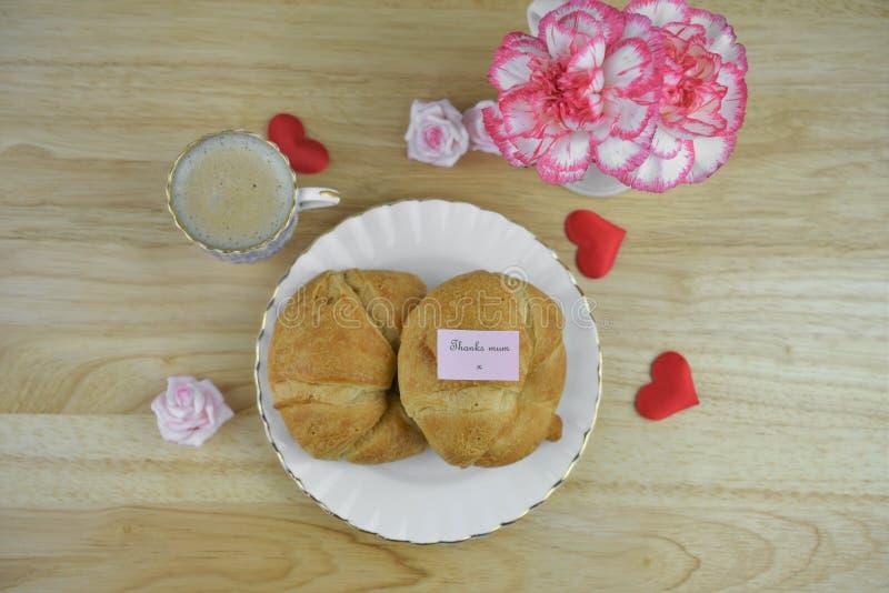 Frühstücken Sie mit warmen Hörnchen und heißem Kaffee für Muttertag mit einer Dankmamaanmerkung lizenzfreies stockfoto