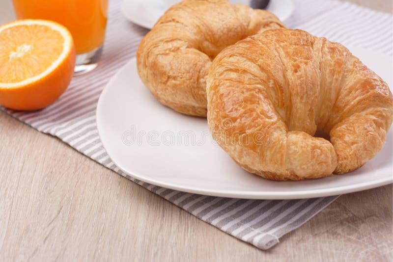 Frühstückshörnchen und Orangensaft lizenzfreie stockfotos