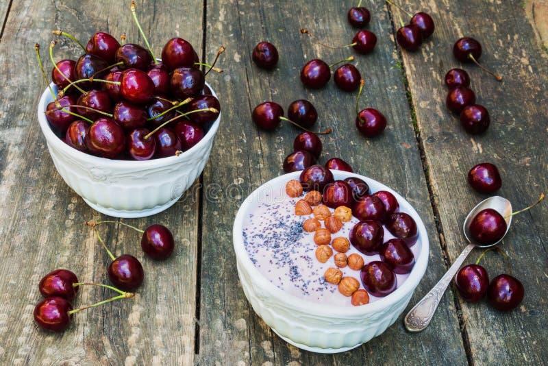 Frühstücksschüssel mit Jogurt, Granola oder muesli oder Haferflocken, frische Kirschen und Nüsse Alter Weinlese-Hintergrund lizenzfreies stockfoto