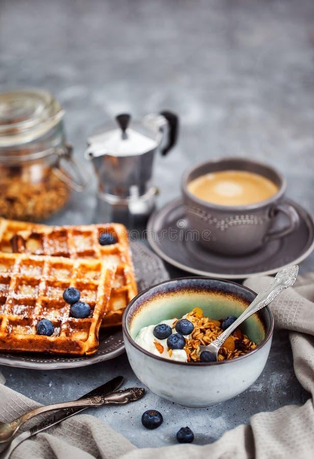 Frühstückstisch mit Granola und Jogurt, frische selbst gemachte belgische Waffeln und heißer schwarzer Kaffee lizenzfreies stockfoto