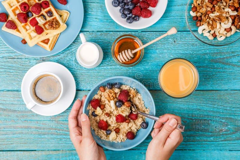 Frühstückstisch mit Waffeln, Hafermehl, Getreide, Kaffee, Saft und frischen Beeren lizenzfreies stockfoto