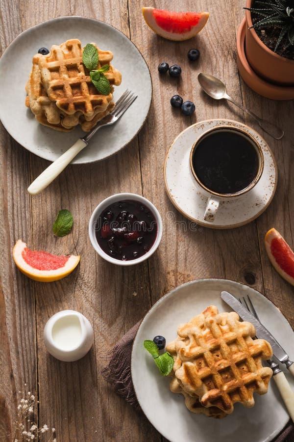 Frühstückstisch mit Waffeln, Kaffee, Früchten und Stau lizenzfreies stockbild