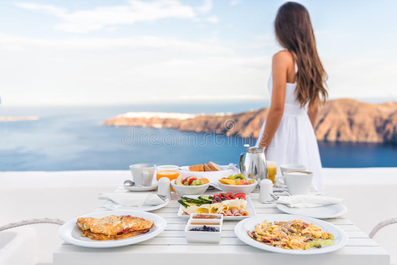 Frühstückstisch und Luxusreise-Frau Santorini stockfotografie