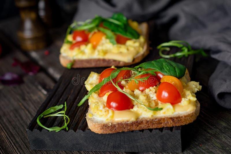 Frühstückstoast: Toastbrot, durcheinandergemischte Eier, Käse und Tomate stockfotos