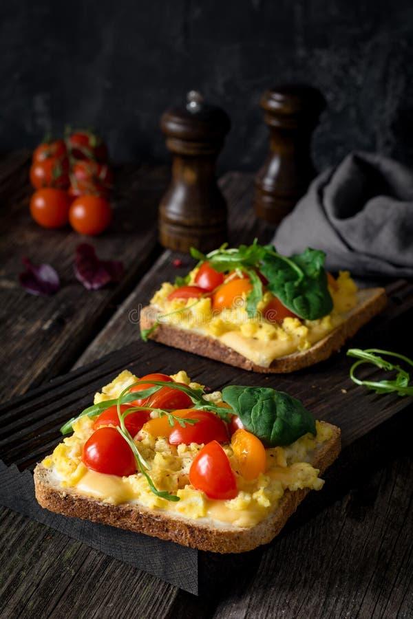 Frühstückstoast: Toastbrot, durcheinandergemischte Eier, Käse und Tomate stockbild