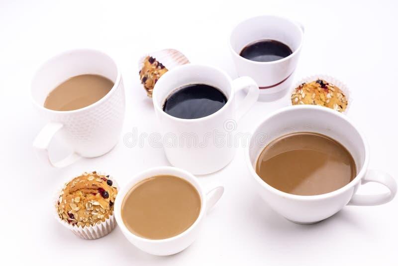 Frühstückszeit-Konzept-verschiedene Kaffeetasse-Muffin-kleine Kuchen über weißer Hintergrund-schwarzem Kaffee Coffe mit Milch lizenzfreies stockbild
