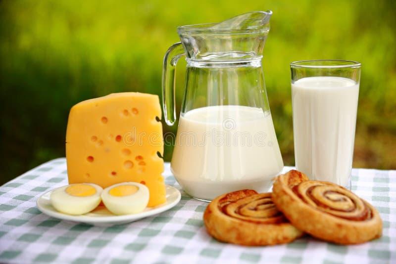 Frühstückszusammensetzung eines Milchkrugs, des Glases Milch, des Stückes Käses und des geschnittenen Eies lizenzfreie stockfotografie