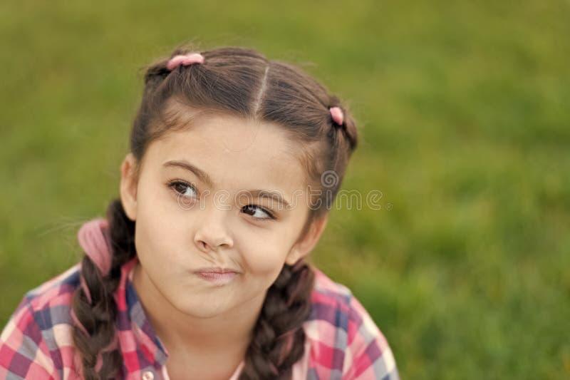 Fr?hjahr-Konzept netter Daydreamer M?dchenkleinkind Freizeit im Park drau?en aufwenden M?dchen sitzen auf Gras im Park Kind stockbilder