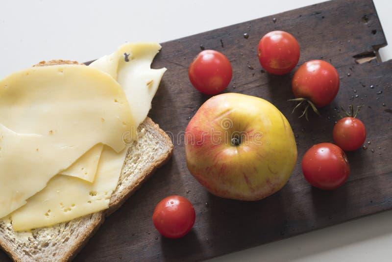 Fr?hst?ck mit Tomaten des holl?ndischen K?ses, des Schwarzbrots, des Apfels und der Kirsche auf h?lzernem Schneidebrett stockbild