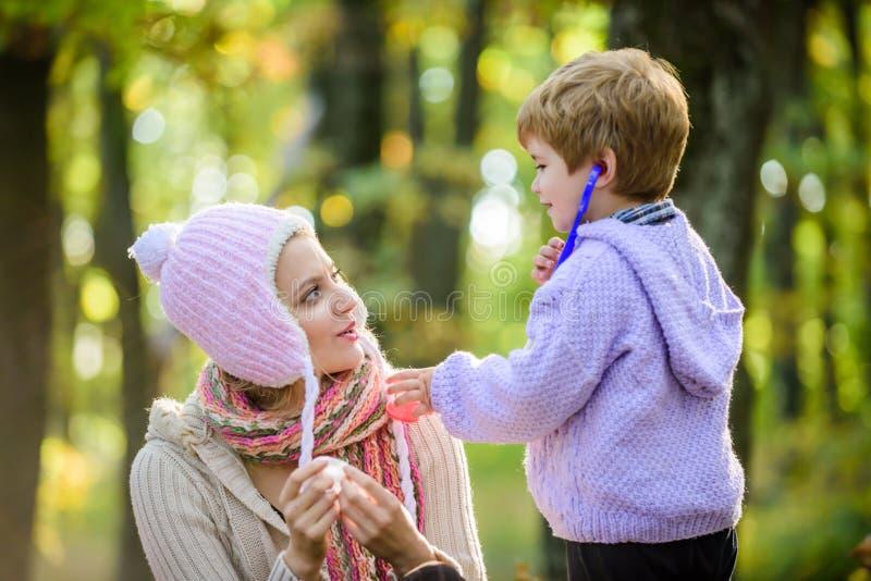 Fr?o estacional D?a feliz de la familia La madre ama a su peque?o ni?o del muchacho Tiempo fr?o Vida sana Familia al aire libre N fotografía de archivo libre de regalías