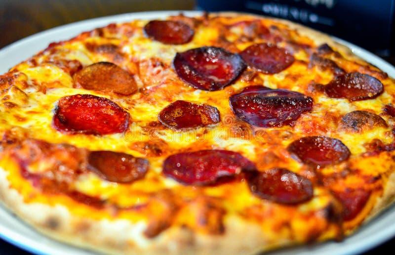 A fraîchement fait la pizza cuire au four complétée avec du fromage et des pepperoni images libres de droits