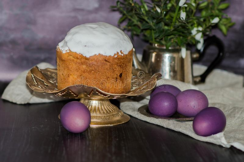 A fraîchement fait le gâteau cuire au four de Pâques sur la table de cuisine couverte de glaçage et décorante l'écrimage des oeuf photographie stock