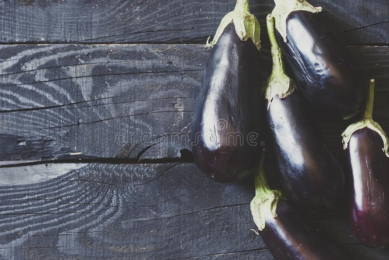 A fraîchement sélectionné les aubergines crues sur le fond en bois photographie stock libre de droits