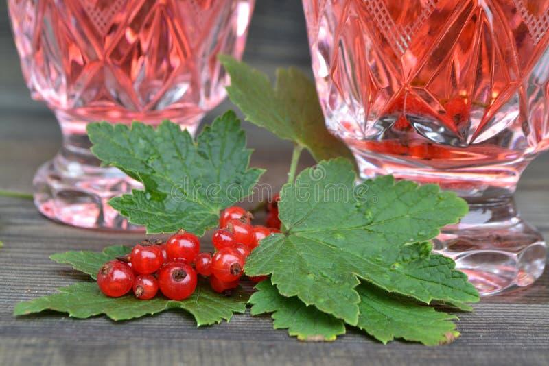 A fraîchement serré le jus rouge, et des groupes de groseilles rouges sur une table en bois noire Fruit cocktail Boisson de limon photographie stock