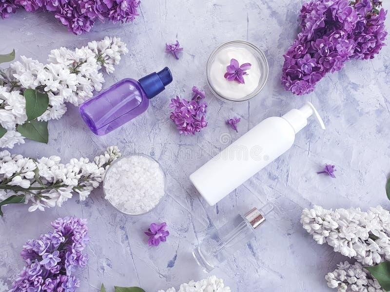 Fraîcheur propre de concept de traitement lilas cosmétique crème de fleur sur un fond concret gris, extrait photos stock