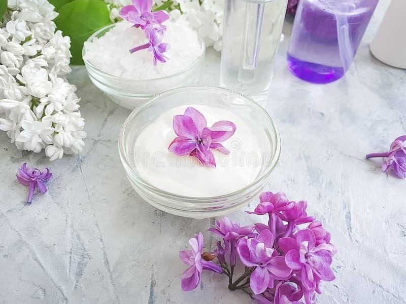 Fraîcheur propre lilas de concept de fleur cosmétique crème sur un fond concret gris, extrait photographie stock