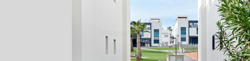 Fra una vista bianca di due case per inverdirsi prato inglese di urbanizzazione residenziale, simili case urbane di architettura  fotografie stock libere da diritti