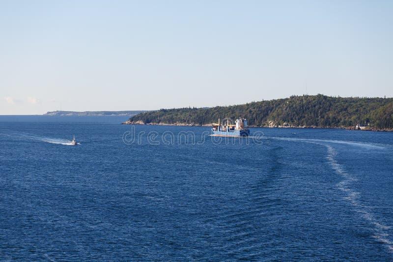 Frachter, der herauf Küste von Kanada im blauen Wasser vorangeht lizenzfreie stockbilder