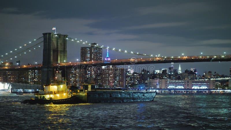 Frachtlastkahnsegel unter der Brooklyn-Brücke in New York auf dem Hintergrund der Nachtlichter von Manhattan lizenzfreie stockbilder