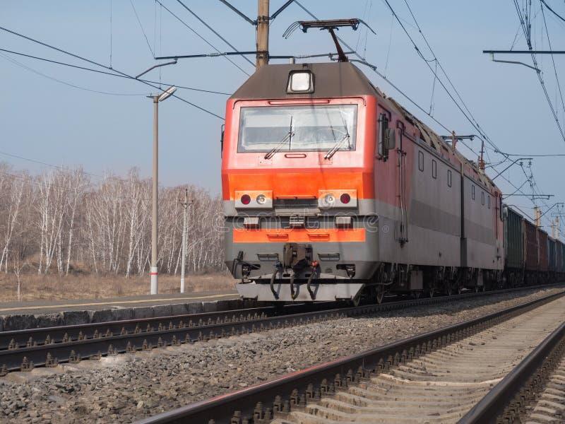 Frachtowy czerwień pociąg przychodzi stacja kolejowa, selekcyjna ostrość obraz royalty free
