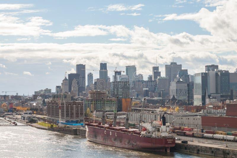 Frachtschiff im Industriehafen von Montreal, Quebec, die Skyline und das Mittelgeschäftsgebiet gegenüberstellend stockfotografie