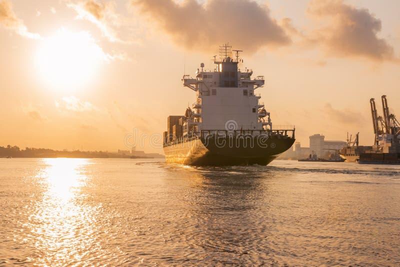 Frachtschiff segelt aus dem Hafen heraus am Abend zum Meer, um Fracht im Behälter zu transportieren lizenzfreie stockfotos