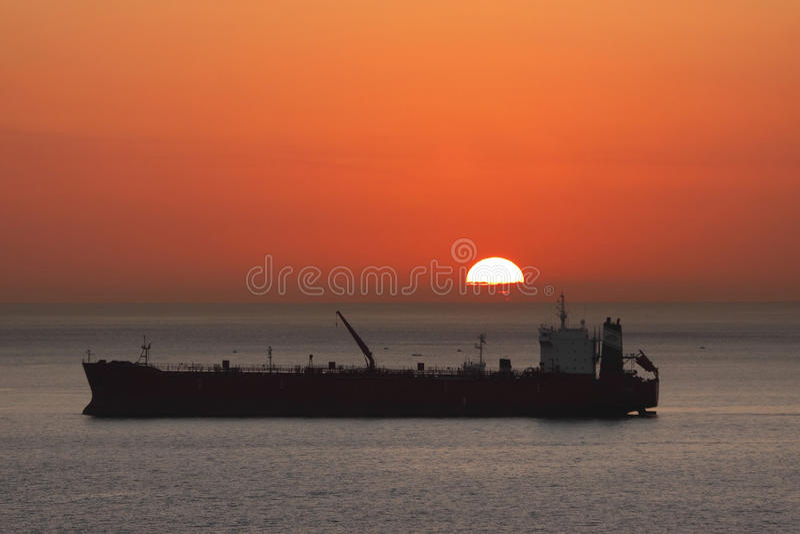 Frachtschiff am Sonnenaufgang lizenzfreies stockfoto