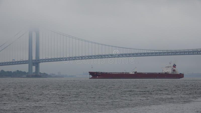 Frachtschiff und Hängebrücke im Nebel stockfotos