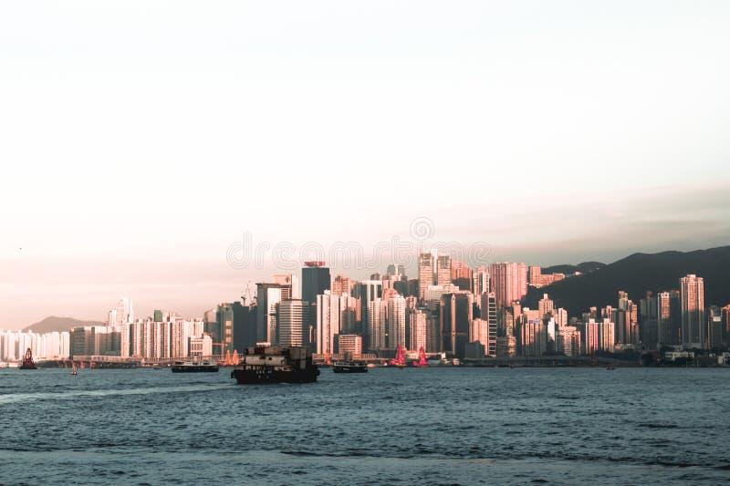 Frachtschiffe, die Victoria Harbor in Hong Kong China während des Sonnenuntergangs kreuzen stockbild