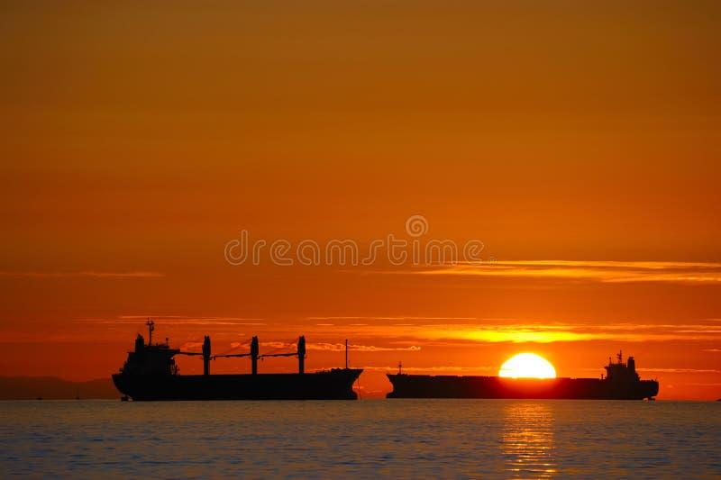 Frachtschiffe am Sonnenuntergang lizenzfreie stockfotos