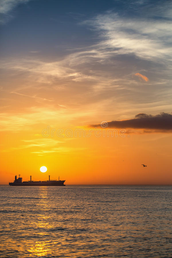 Frachtschiffsegeln auf Sonnenaufgang nahe dem Strand lizenzfreie stockfotografie