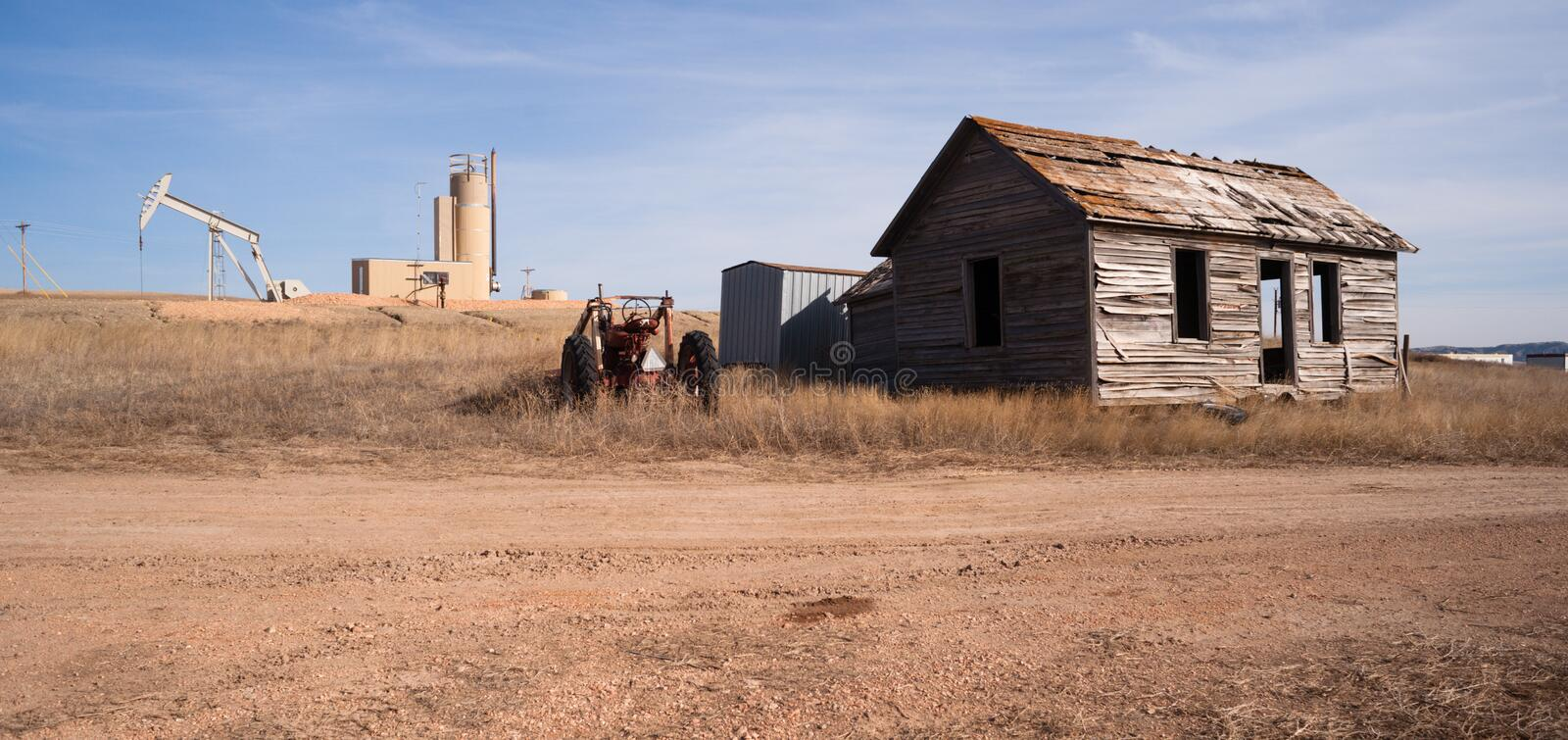 Fracking Operation Built on Previous Farmland Abandoned Cabin. An abandoned tractor and cabin sit in the foreground of a fracking oil pump jack royalty free stock images