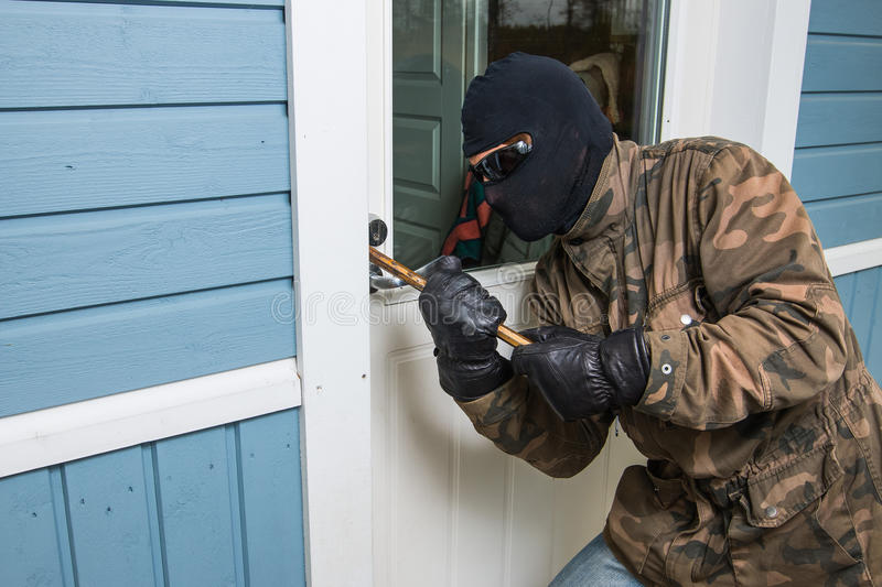 Fractional man breaking into a residential building in Finland. royalty free stock photography