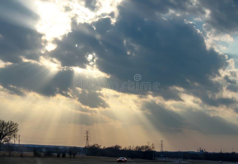 Fractura ligera a través de las nubes sobre la carretera con los coches en el crepúsculo con las torres eléctricas con la fábrica imagen de archivo libre de regalías