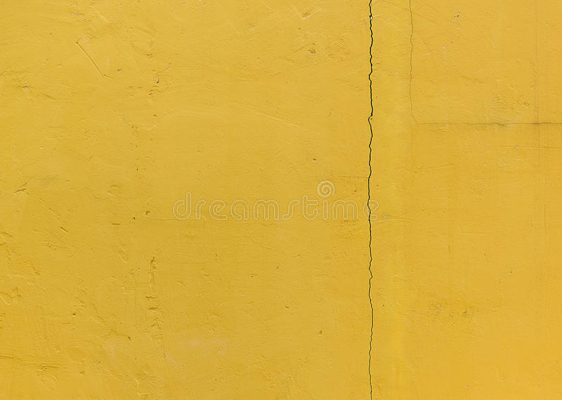 Fracture in the wall, Yellow grunge cement wall, texture background royalty free stock photo