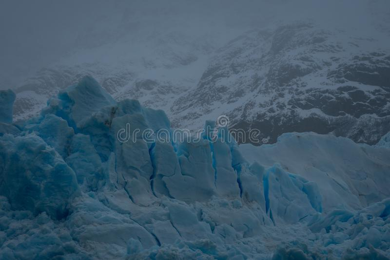 Fractured blue ice on a glacier in Argentina. In a close up view showing the cracks and fissures on a misty cold day royalty free stock images