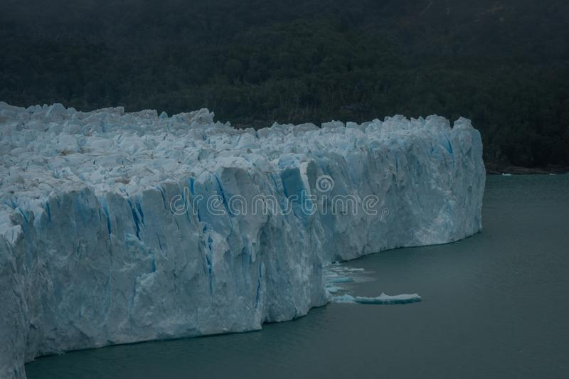 Fractured ice at the end of a glacier. With shards calving or breaking off into the melt water below in Argentina, South America royalty free stock photo