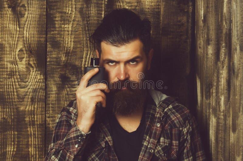 Fragancia masculina y perfumería Cosméticos Hombre barbudo que presenta con la botella negra del perfume o del cologne foto de archivo