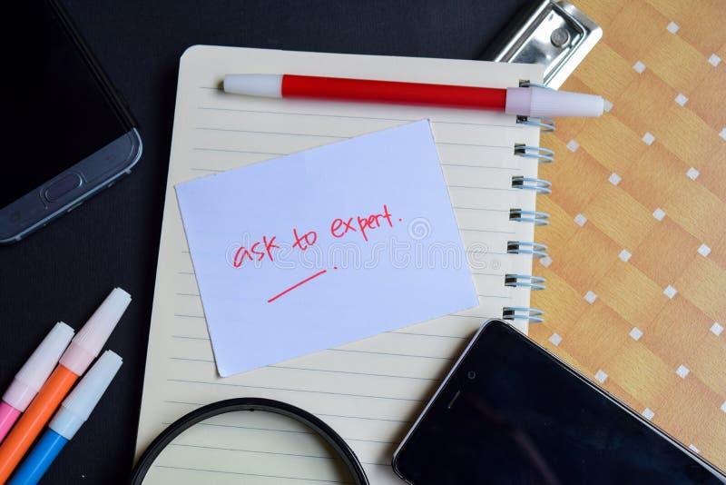 Fragen Sie zum sachverständigen Wort, das auf Papier geschrieben wird Fragen Sie zum sachverständigen Text auf Arbeitsbuch, Techn lizenzfreies stockfoto