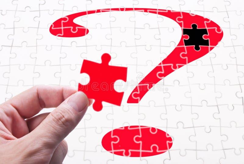 Fragezeichen, Hand und Puzzlespielspiel stockfotografie
