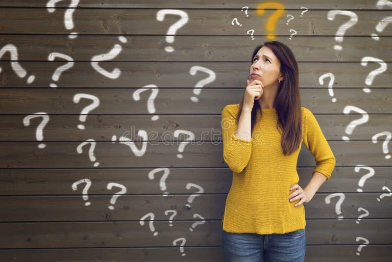 Fragezeichen mit junger Frau in einer durchdachten Haltung lizenzfreie stockbilder