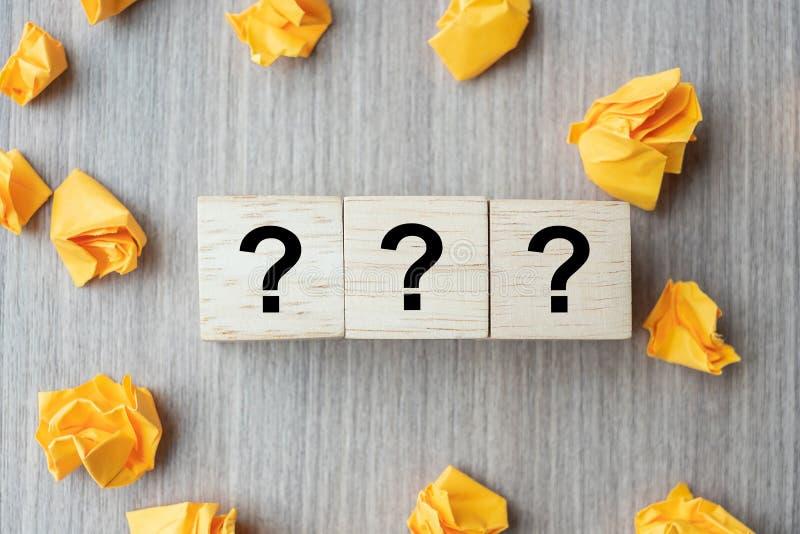 Fragezeichen? Wort mit hölzernem Würfelblock und gelbem zerfallenem Papier auf Tabellenhintergrund FAQ-Frequenz stellte Fragen, lizenzfreie stockfotos